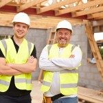 Portrait Of Carpenter With Apprentice Working On Site